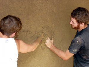 Volunteers applying earthen plaster